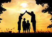 Fotografie Silhouette, group of happy children playing on meadow, sunset, s