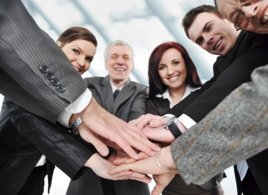 Group of happy smiling executives placing their hands together