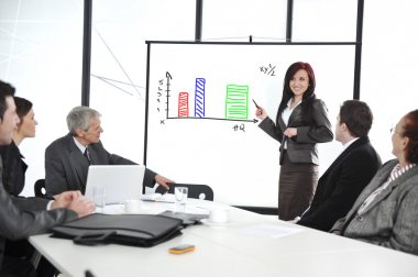 Business meeting - group of in office at presentation with flipchart