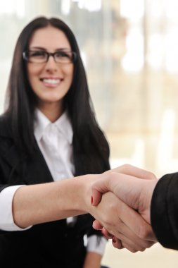 Business woman smiling and handshaking over white background