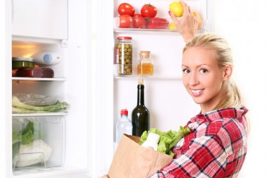 Young woman is putting a food into the fridge
