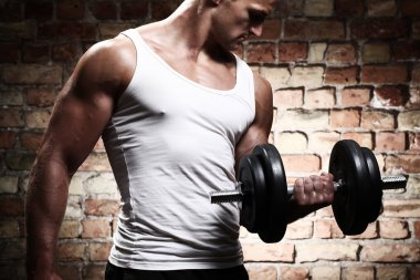 Muscular guy doing exercises with dumbbell