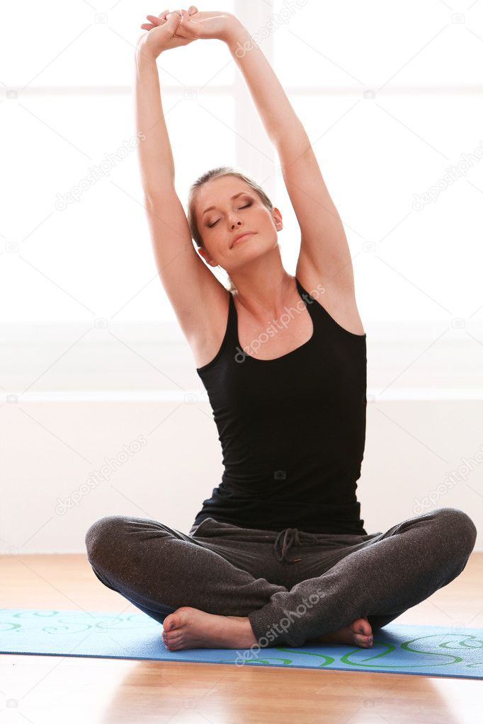 belle femme faisant des exercices d 39 yoga la maison photographie yekophotostudio 12791395. Black Bedroom Furniture Sets. Home Design Ideas