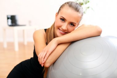 Beautiful woman with fitness ball at home