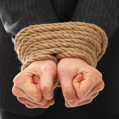 Close up of businessman hands tied with rope