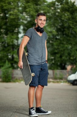 Handsome guy with headphones and skateboard