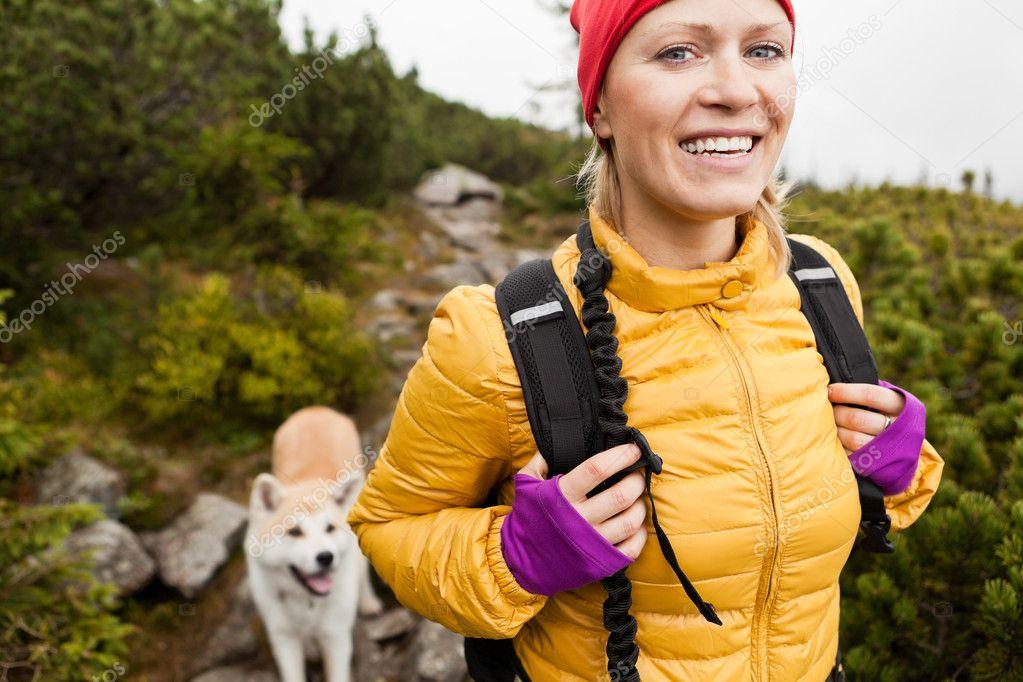 Woman hiking in mountains with akita dog, Karkonosze Mountain Range stock vector