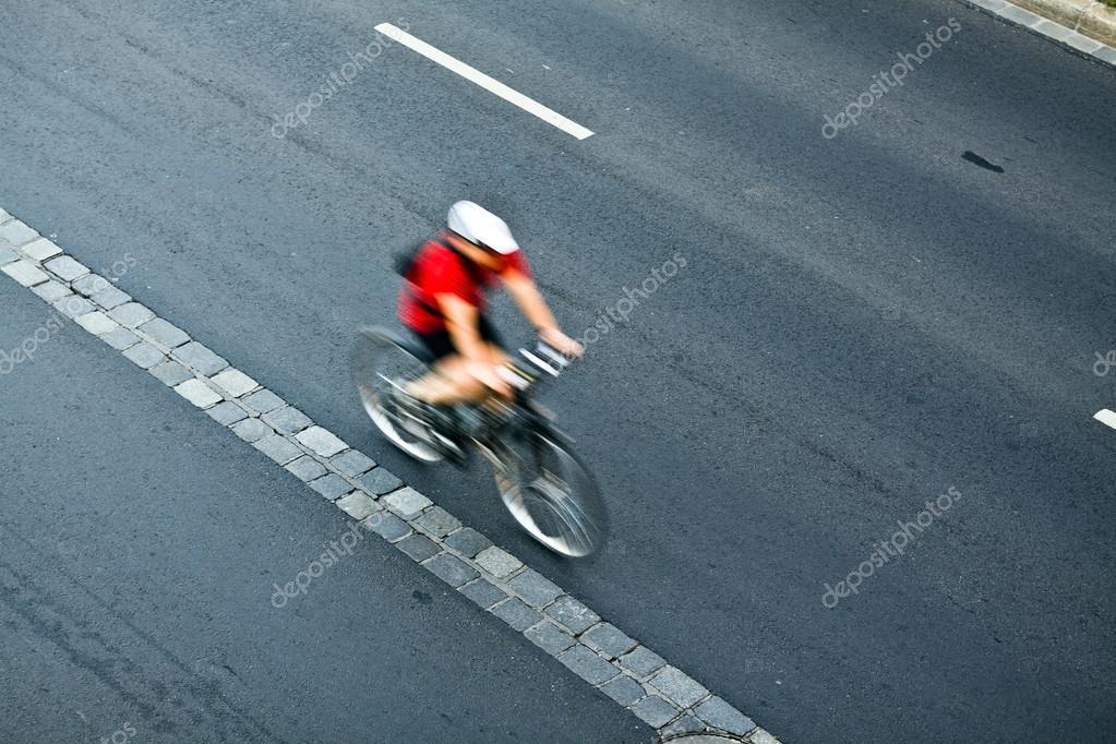 Man cycling on city street, motion blur