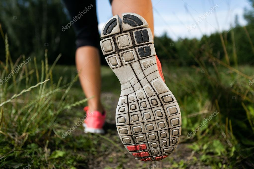 Woman and running shoes in forest, exercising in nature