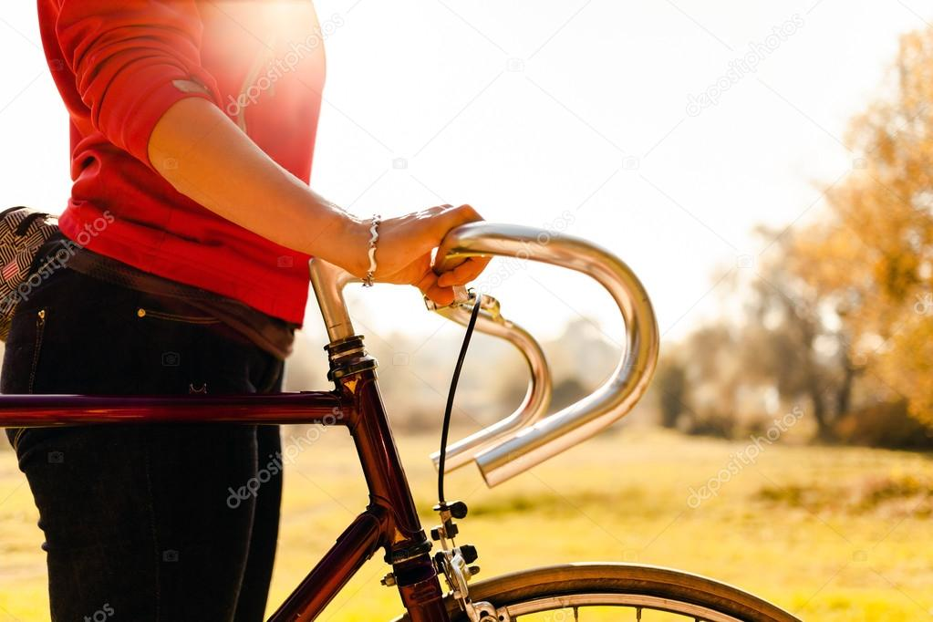 Woman cycling on bicycle in autumn park