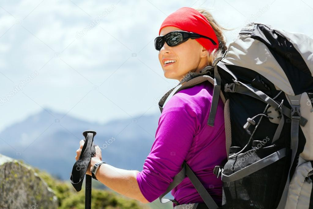 Woman hiking with backpack in mountains