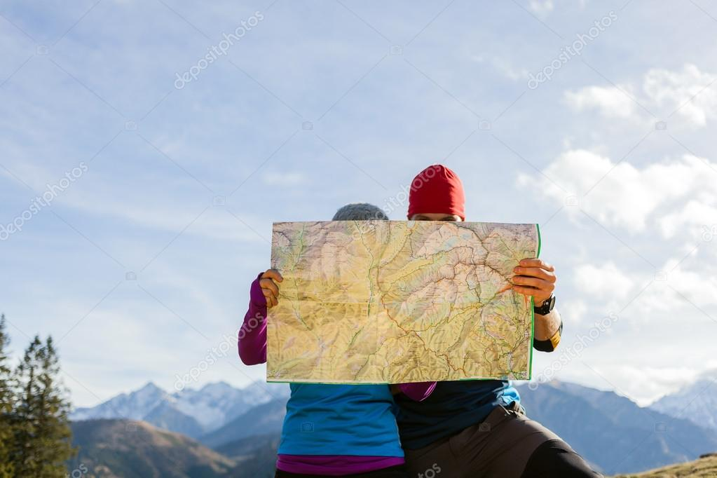 Couple hiking with map in mountains