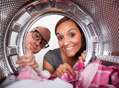 Young couple doing laundry View from the inside of washing machine.