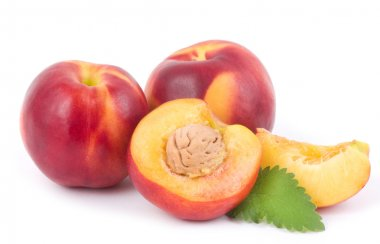 Fresh nectarines whole end half with green leaves on white background