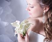 krásná nevěsta s elegantní make-up v bílých šatech