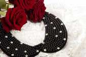 Fotografie Pearl necklace with red roses