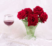 Fotografie Beautiful red roses in vase with wine glass