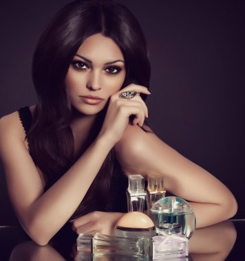 Beautiful young woman with perfume bottle
