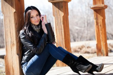 young brunette woman sitting leaning against a wooden post