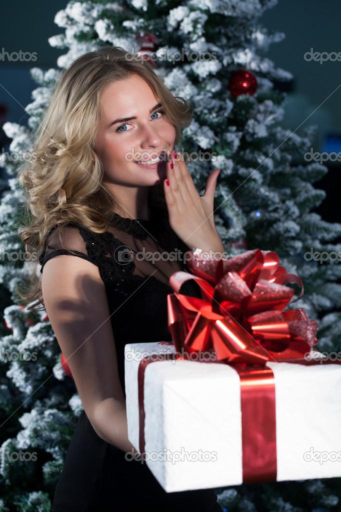 Mädchen mit Weihnachtsgeschenke auf Weihnachtsbaum-Hintergrund ...
