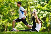 Fotografie pár dělá protahovací cvičení po běhání