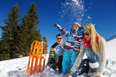Family having fun on fresh snow at winter vacation