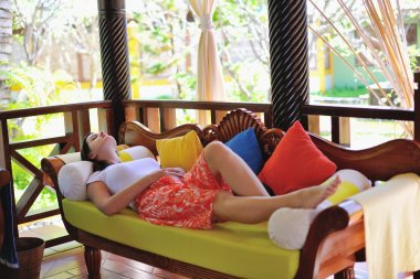 Woman resting at couch, tropical resort