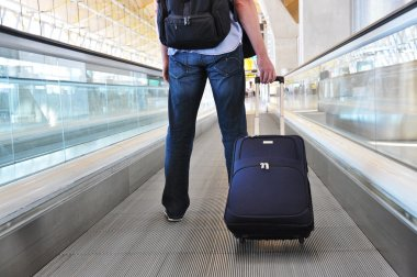 Traveller with a suitcase on the speedwalk