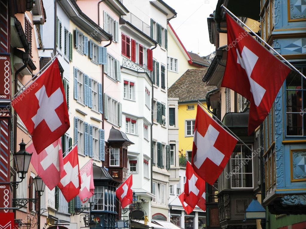 Old street in Zurich decorated with flags for the Swiss Nationa