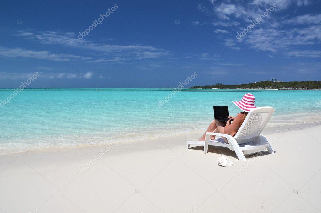 Girl with a laptop on the tropical beach. Exuma, Bahamas