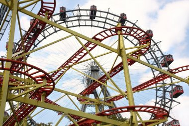 Roller coaster and large ferris wheel in Prater, Vienna, Austria