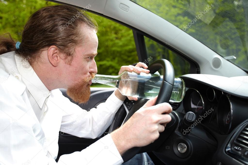 homme ivre en voiture avec une bouteille d 39 alcool photographie vladacanon 45456341. Black Bedroom Furniture Sets. Home Design Ideas