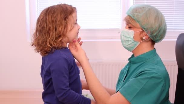 Ärztin untersucht Kehle des kleinen Mädchens