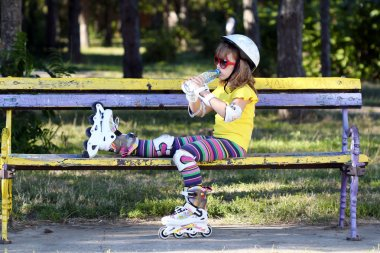 little girl with roller skates sitting on bench and drink water
