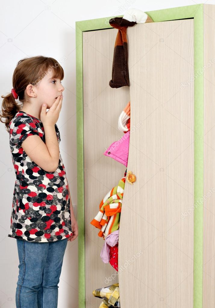 Shocked little girl looking into a messy closet