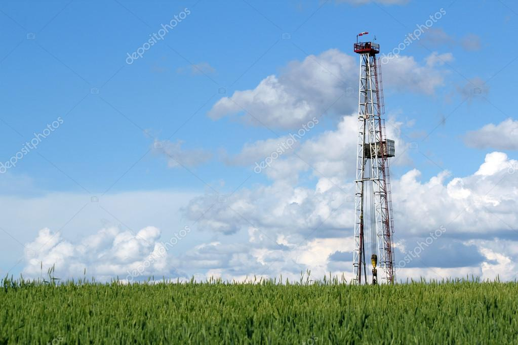 oil drilling rig on green wheat field
