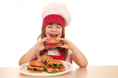 hungry little girl cook eating sandwich