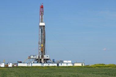 land oil drilling rig on green field landscape