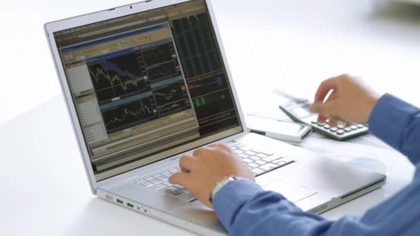Üzletember, tőzsde, a laptop számítógép ellenőrzése