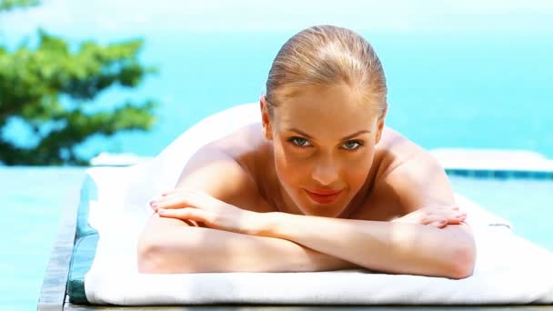 Smiling woman on spa bed next to swimming pool