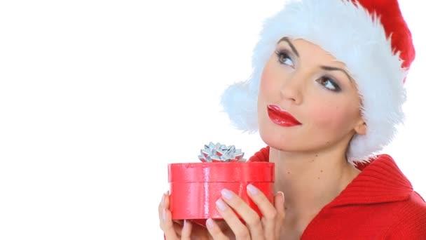 sexy dívka v klobouku santa claus ukazující dar v poli