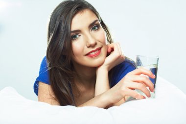 Portrait of woman holding glass in bed
