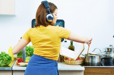 Woman cooking food with fun and listen music