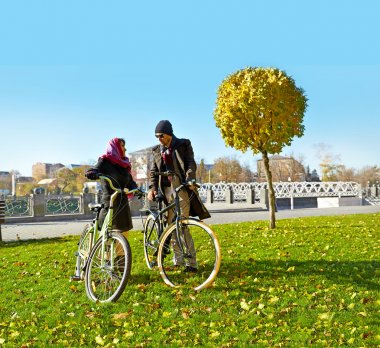 Young couple walks  in the autumn park with a bicycle