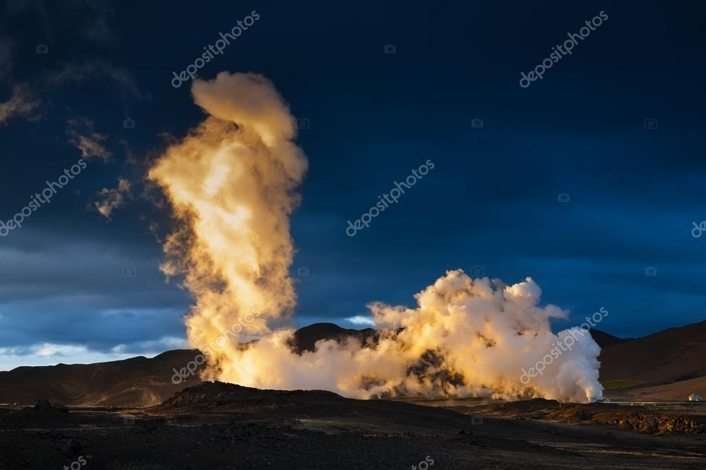 Steam erupting from geothermal power station at sunset