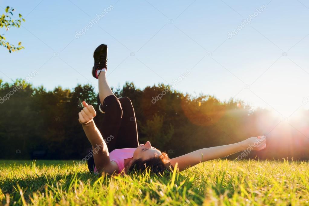 Joven bonita mujer acostada y streching ella misma en la hierba en el  atardecer de verano. relajación faf7b120213e