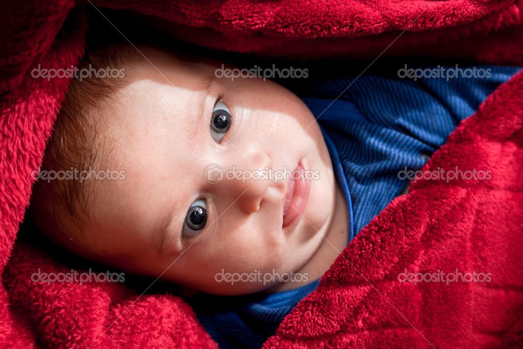 hermoso bebé de 3 meses en cama cubierto con una manta roja — Foto ...