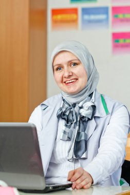 Beautiful young muslim woman using laptop in office