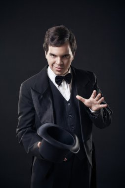 Magician showing tricks with top hat isolated on dark background