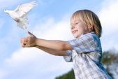 Fotografie malý chlapec uvolňuje bílého holuba na obloze